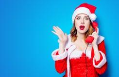 Ragazza di Santa Clous in vestiti rossi con il microtelefono fotografie stock