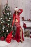 Ragazza di Santa di Natale con la borsa dei regali sorpresa Bello modello sorridente della donna, capelli ricci lunghi Signora el Immagine Stock Libera da Diritti