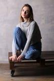 Ragazza di seduta che posa su una piattaforma Fondo grigio Fotografia Stock Libera da Diritti