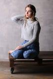 Ragazza di seduta che tocca i suoi capelli Fondo grigio Fotografie Stock Libere da Diritti