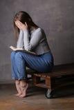 Ragazza di seduta con il libro che copre il suo fronte Fondo grigio Immagine Stock
