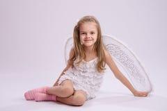 Ragazza di seduta in costume di angelo Immagine Stock