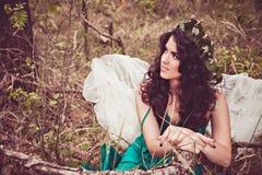 Ragazza di seduta graziosa con le ali di angelo Fotografia Stock