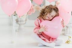 Ragazza di sei anni sveglia in vestito rosa con i palloni rosa sotto forma di cuore fotografia stock