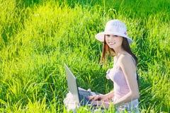 Ragazza di sorriso che per mezzo del computer portatile Immagine Stock Libera da Diritti