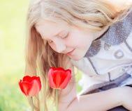 Ragazza di sorriso con i tulipani all'aperto Fotografie Stock Libere da Diritti