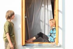 Ragazza di sorveglianza del ragazzo che si siede nella finestra Immagine Stock Libera da Diritti