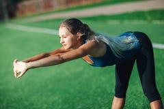 Ragazza di sport in camicia blu e ghette che fanno allenamento di ginnastica su un campo di football americano Forma fisica, spor Fotografie Stock Libere da Diritti