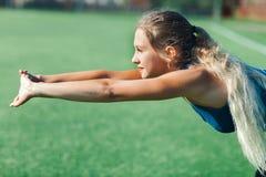 Ragazza di sport in camicia blu e ghette che fanno allenamento di ginnastica su un campo di football americano Forma fisica, spor Fotografia Stock Libera da Diritti