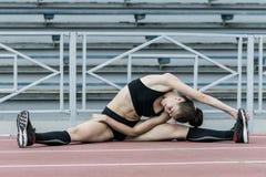 Ragazza di sport che fa allungando esercizio in stadio Immagini Stock