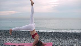 Ragazza di sport che fa headstand su una spiaggia archivi video