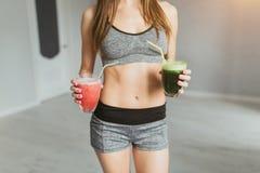 Ragazza di sport dopo che l'esercizio si rilassa in una stanza luminosa e nelle bevande del cocktail Fotografia Stock