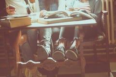 Ragazza di tre una giovane studenti che si siede nella biblioteca Immagini Stock