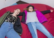 Ragazza di tredici anni con la sorella di undici anni che si rilassa su un grande cuscino rosso Immagine Stock