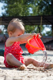 Ragazza di un anno con un secchio rosso alla spiaggia Fotografie Stock Libere da Diritti