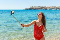 Ragazza di vacanza della spiaggia di estate che prende a divertimento la foto mobile del selfie con lo smartphone Ragazza che ind immagini stock libere da diritti