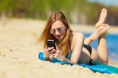 Ragazza di vacanze estive con il telefono che si abbronza sulla spiaggia Immagine Stock Libera da Diritti