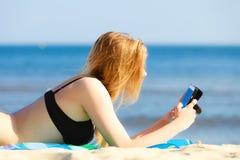 Ragazza di vacanze estive con il telefono che si abbronza sulla spiaggia Fotografie Stock Libere da Diritti
