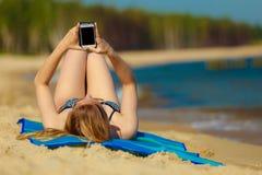 Ragazza di vacanze estive con il telefono che si abbronza sulla spiaggia Fotografia Stock Libera da Diritti
