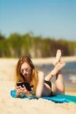 Ragazza di vacanze estive con il telefono che si abbronza sulla spiaggia Immagini Stock
