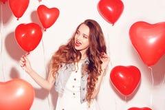 Ragazza di Valentine Beauty con gli aerostati rossi che ride, sul fondo bianco Bella giovane donna felice Il giorno della donna P immagini stock libere da diritti