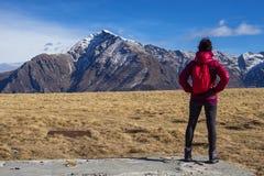 Ragazza di viaggiatore con zaino e sacco a pelo nelle alpi immagini stock
