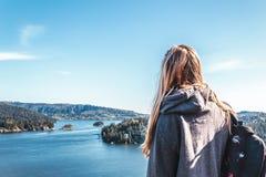 Ragazza di viaggiatore con zaino e sacco a pelo sopra la roccia della cava a Vancouver del nord, BC, Ca Immagine Stock Libera da Diritti