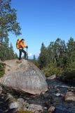Ragazza di viaggiatore con zaino e sacco a pelo su una roccia che guarda la mappa di itinerario Fotografia Stock Libera da Diritti