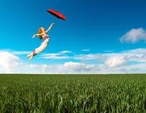 Ragazza di volo con l'ombrello rosso Immagini Stock