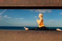 Ragazza di yoga che medita e che si rilassa nella posa di yoga, vista di oceano Immagini Stock Libere da Diritti