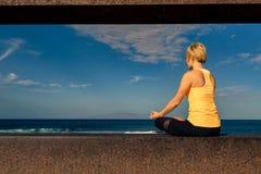 Ragazza di yoga che medita e che si rilassa nella posa di yoga, vista di oceano Immagine Stock