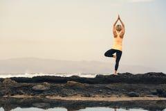 Ragazza di yoga che medita e che si rilassa nella posa di yoga, vista di oceano Fotografie Stock Libere da Diritti