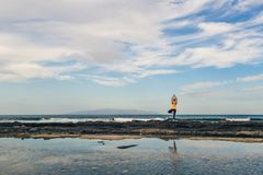 Ragazza di yoga che medita e che si rilassa nella posa di yoga, vista di oceano Immagini Stock
