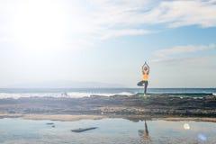 Ragazza di yoga che medita e che si rilassa nella posa di yoga, vista di oceano Fotografia Stock Libera da Diritti