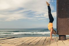 Ragazza di yoga che medita e che si rilassa nella posa di yoga, vista di oceano Immagine Stock Libera da Diritti