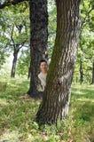 Ragazza dietro l'albero il giorno di estate caldo Fotografia Stock