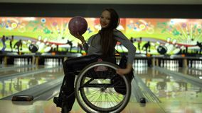 Ragazza disabile attraente in una sedia a rotelle divertendosi nel bowling, dancing con una palla da bowling stock footage