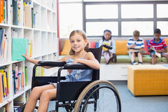 Ragazza disabile della scuola che seleziona un libro a partire dallo scaffale per libri in biblioteca immagine stock libera da diritti