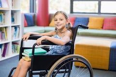 Ragazza disabile della scuola con i libri in biblioteca Fotografie Stock
