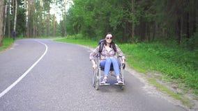 Ragazza disabile in una sedia a rotelle con un viaggio dello zaino stock footage
