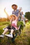Ragazza divertendosi con l'agricoltore nell'orto fotografie stock