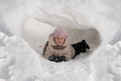 Ragazza divertente che gioca in un iglù della neve un giorno di inverno soleggiato Fotografie Stock Libere da Diritti