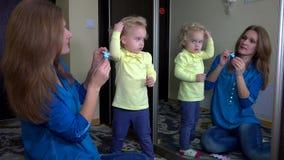 Ragazza divertente con il perno in capelli con sua madre davanti allo specchio archivi video
