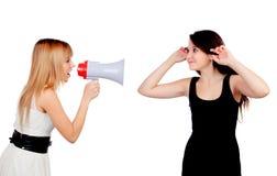 Ragazza divertente con un megafono che parla con suo amico Immagine Stock