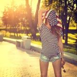 Ragazza divertente dei pantaloni a vita bassa con la bandiera di U.S.A. sulla sua testa Fotografia Stock