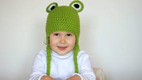 Ragazza divertente del bambino in cappello verde che sorride e che ride Bambino felice sveglio che gioca e che esamina macchina f stock footage