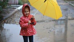 Ragazza divertente del bambino che salta e che gioca nelle pozze in tempo piovoso sotto un ombrello stock footage