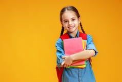 Ragazza divertente della ragazza della scuola del bambino su fondo giallo immagine stock libera da diritti