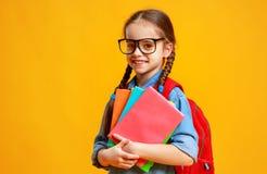 Ragazza divertente della ragazza della scuola del bambino su fondo giallo fotografia stock