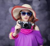 Ragazza divertente della testarossa in cappello con la macchina fotografica e bokeh a fondo fotografie stock libere da diritti